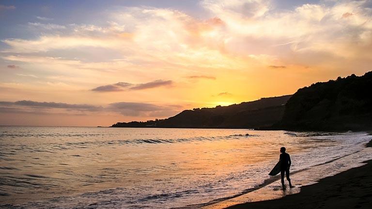 Ein Surfer an einem Strand einer Azoren-Insel