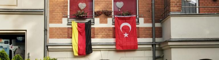 Eine türkische und eine deutsche Fahne an einem Haus.