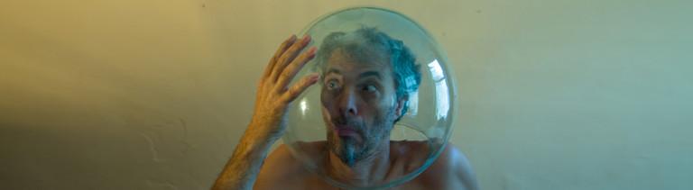 Ein mann sitzt bei sich zu hause am Tisch und hat eine Glaskugel auf dem Kopf. Symbolisch für Astronaut, Kosmonaut oder Taucher.