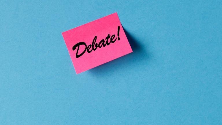 """Ein Post-it auf dem """"Debate"""" steht."""