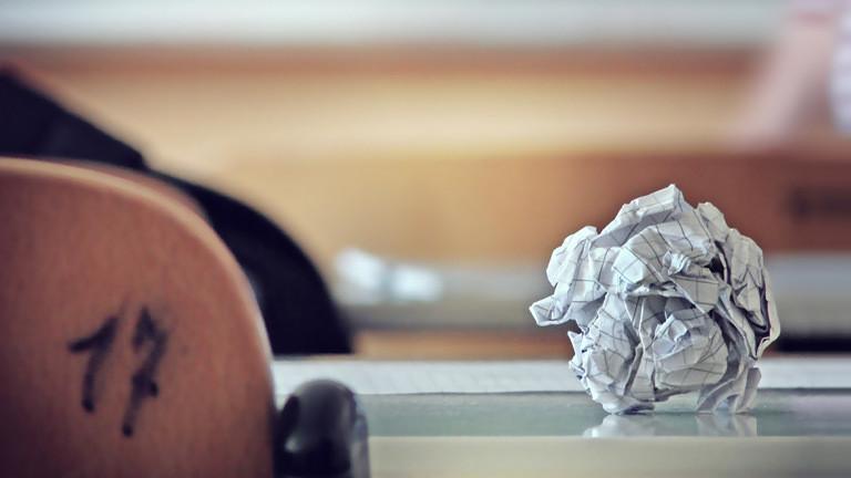 Zerknüllter Zettel auf einer Schulbank.