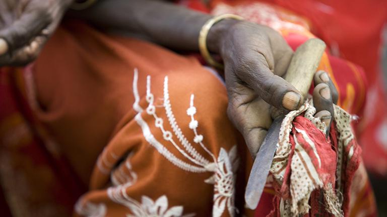Eine Hand hält ein rostiges Messer, das zur Beschneidung von jungen Mädchen benutzt wurde