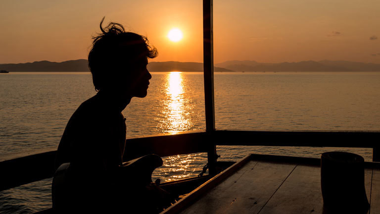 Gitarrenspieler bei Sonnenuntergang am Meer