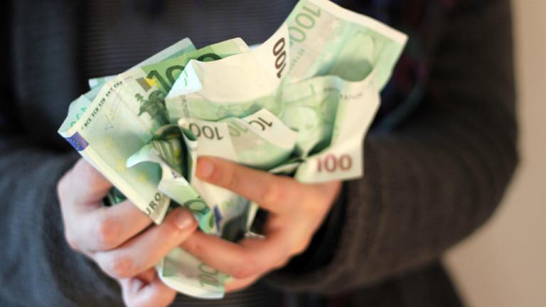 Eine Person hält viele Hundert-Euro-Scheine in beiden Händen.