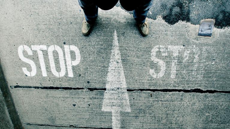 Ein Mann steht vor einem Pfeilmarkierung auf dem Boden neben dem das Wort Stop geschrieben steht.