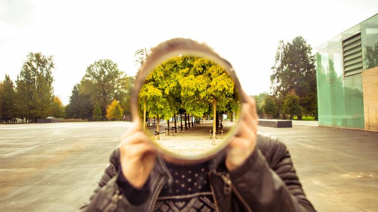 Ein Mann mit einem Spiegel vor seinem Gesicht.