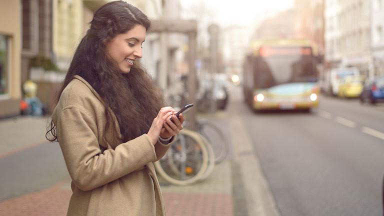 Frau steht an der Straße und wartet auf einen Bus, während sie auf ihrem Handy rumtippt.
