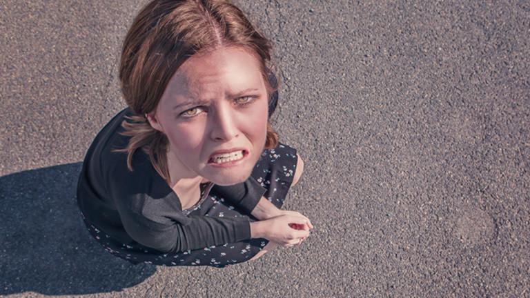 Eine Frau hockt und guckt traurig und verzweifelt nach oben in die Kamera.