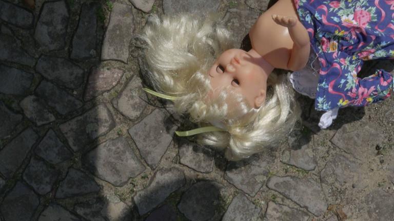 Eine kaputte Puppe liegt auf der Straße.