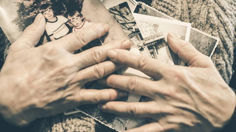 Eine ältere Frau hält Fotos in ihren Händen.