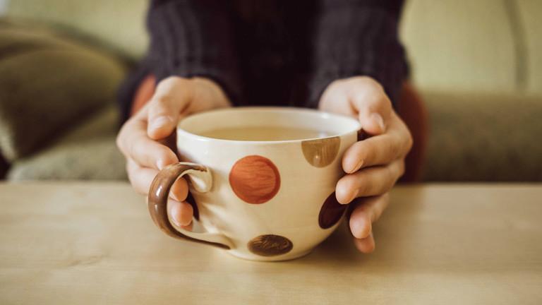 Eine junge Frau hält eine Tasse Tee in ihrer Hand.