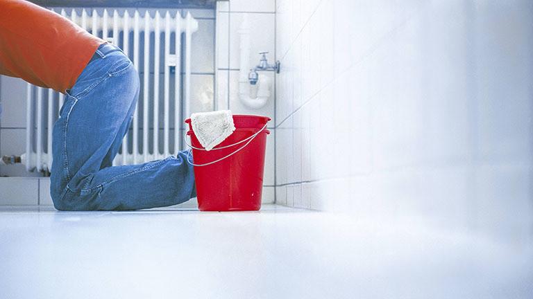 Ein Mann putzt auf Knien ein Badezimmer.