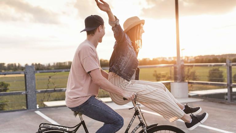 Eine Frau sitzt vorne auf dem Fahrrad, das von einem jungen Mann gefahren wird. Sie breitet die Arme aus und lacht. Symbolbild für Freiheit und Optimismus.