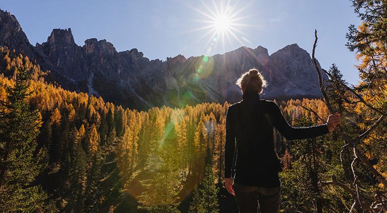 Eine Frau steht alleine in der Natur und schaut in Richtung einer Hügelkette.
