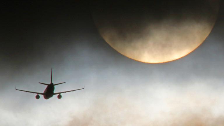 Ein Flugzeug fliegt dem Mond entgegen. Es ist eher düster.