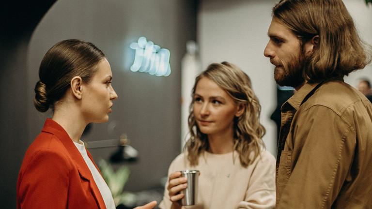 Zwei Frauen und ein mann stehen zusammen und sprechen miteinander.