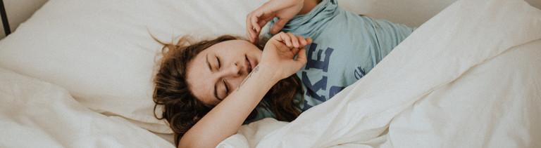 Frau liegt im Bett und schläft ein oder wacht auf