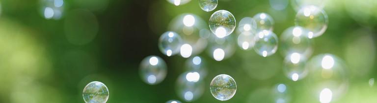 Seifenblase vor grünem Hintergrund.