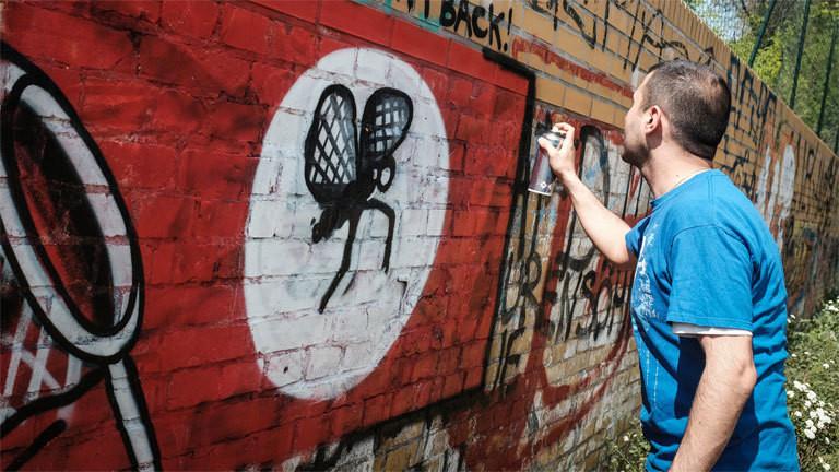 Ein Graffiti-Sprayer übersprüht ein Hakenkreuz.