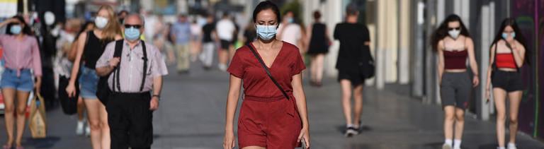 Fußgänger, die Masken trragen.
