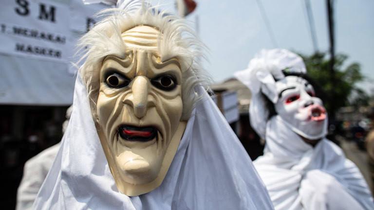 Menschen, die mit weißen Tüchern und Masken als indonesische Pecong-Geister verkleidet sind.