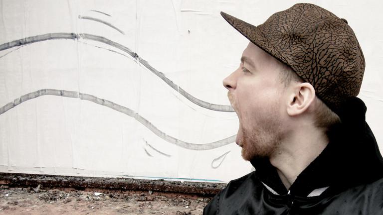 Ein Mann steht vor einer Wandzeichnung.