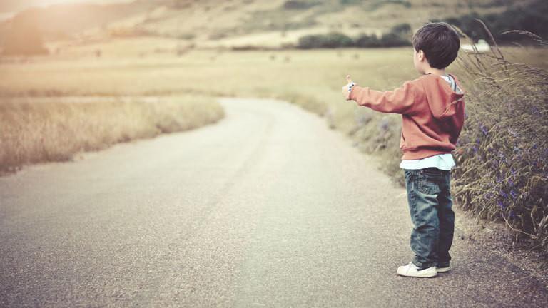 Ein kleiner Junge hält an einer Straße den Daumen raus und will mitgenommen werden.