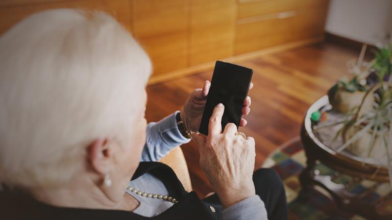 Eine Seniorin sitzt im Wohnzimmer und tippt auf einem Smartphone.
