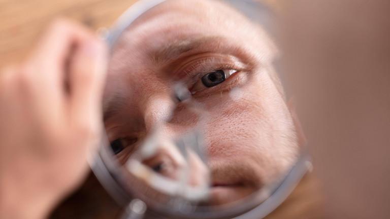 Ein Mann blickt in einen zerbrochenen Spiegel.
