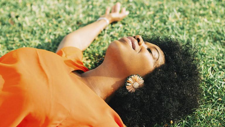 Frau mit Afro-Haaren liegt im Gras.