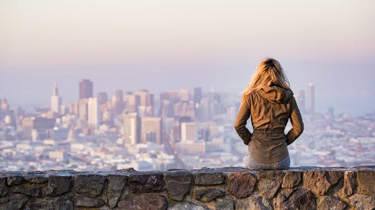 Eine Frau schaut von einer Mauer auf einem Berg auf die Stadt herab.