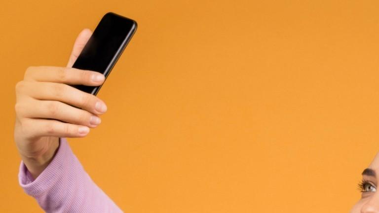 Frau hält ein Handy hoch um ein Selfie zu machen.