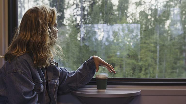 Eine junge Frau schaut aus einem Zugfenster.