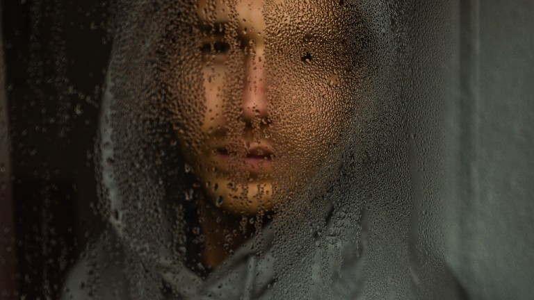 Mann guckt einsam und traurig aus einem verregneten Fenster.