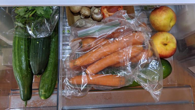 Gurken, Karotten, Äpfel in einer Kühlschrank-Schublade