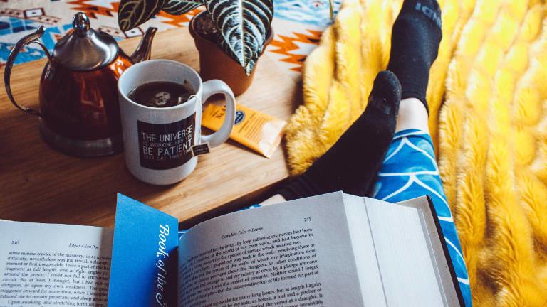 Eine Person liegt mit Tee und Buch auf dem Sofa