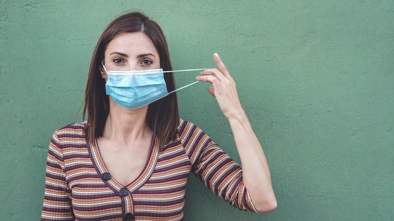 Frau mit medizinischer Maske, die eine medizinische Schutzmaske hält