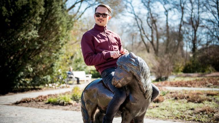Ein Mann sitzt auf einem zu kleinen Bronzepony.