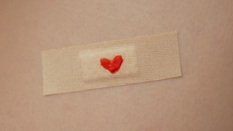 Pflaster mit rotem kleinen Herzchen auf dem Arm.