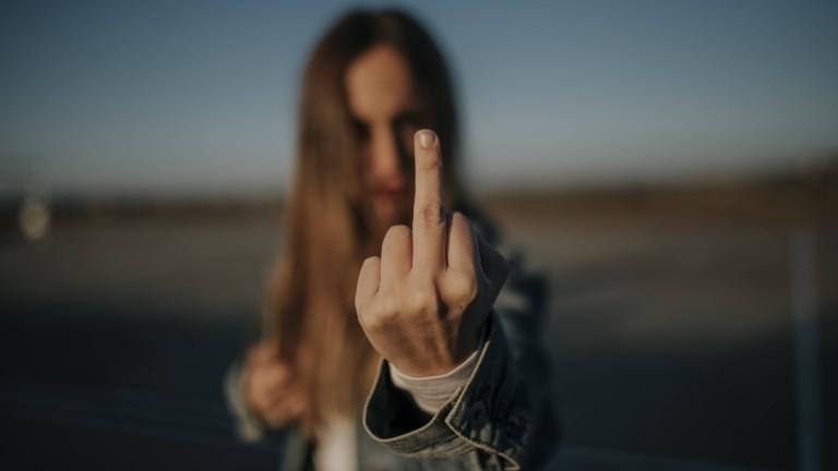 Eine Frau hält ihren Mittelfinger in die Kamera.