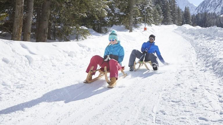 Eine Frau und ein Mann sitzen jeweils auf einem Schlitten und fahren einen Berg hinunter.