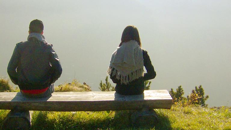 Zwei Menschen sitzen auf einer Bank fotografiert von hinten.