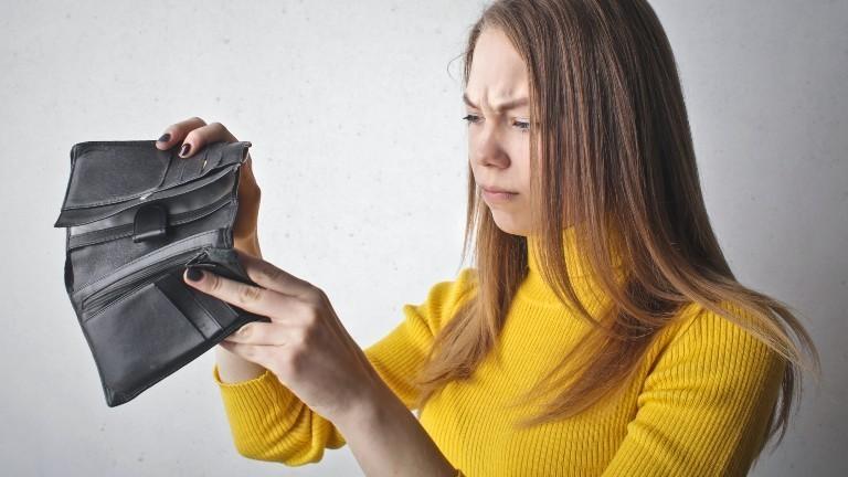Eine junge Frau schaut verärgert in ein leeres Portemonnaie.