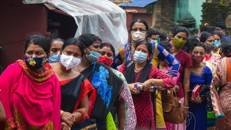 In Kalkutta stehen Menschen in einer Warteschlange für die Coronavirus-Impfung an.