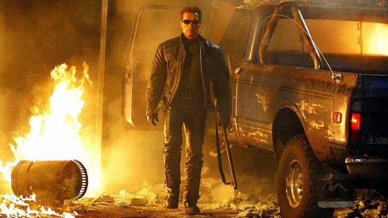 """Der Terminator (Arnold Schwarzenegger) steht im Kinofilm """"Terminator 3 - Rebellion der Maschinen"""" neben einem Autowrack."""