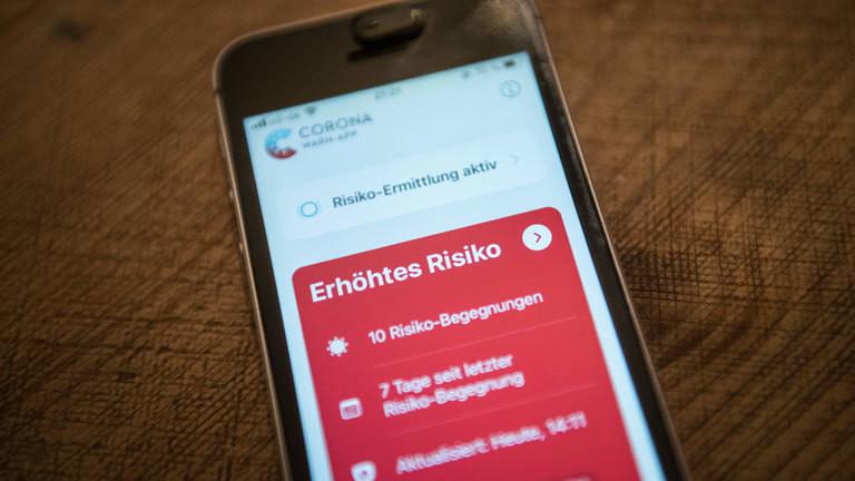 Mobiltelefon, das auf dem Display die Corona-App anzeigt.