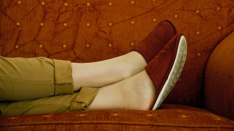 Mann oder Frau liegt mit Pantoffeln auf der Couch