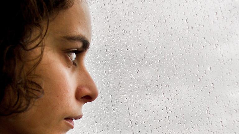 Eine junge Frau sitzt vor einem Fenster. Draußen regnet es.