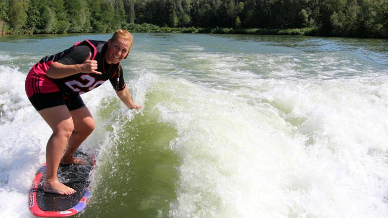 Caro Köhler auf einem Wakeboard im Wasser.