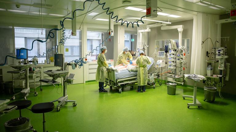 In einem Krankenhaus stehen Pfleger in Schutzkleidung um einen Patienten.